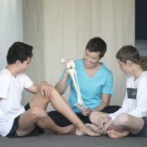 Boys with femur bone education by osteopath